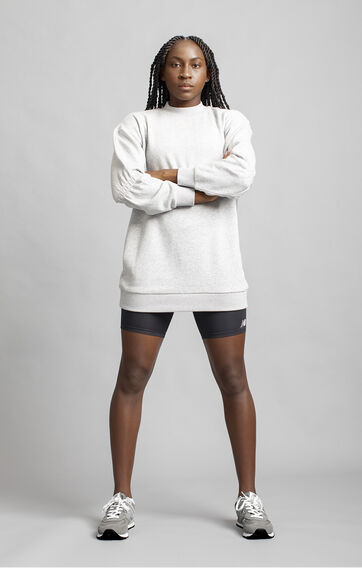Coco Gauff standing against grey studio backdrop with arms crossed while wearing grey NB apparel and shoes.